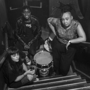 black and white image, three band members pose on a staircase, with drums in the middle of them